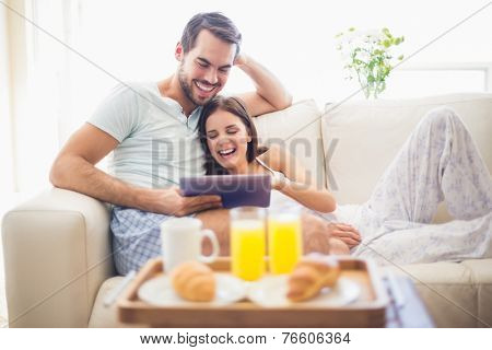 Cute couple relaxing on couch with tablet at breakfast at home in the living room poster