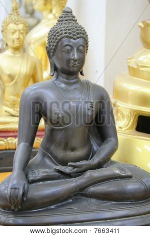 Ancient Black Statue Of A Calm Buddha In A Meditation Pose