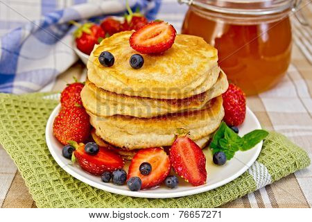 Flapjacks with strawberries and blueberries with napkin