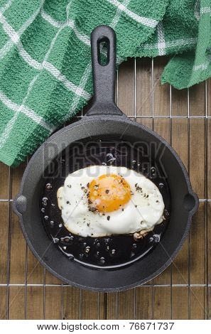 fried egg with crushed pepper and coarse salt in a cast iron pan on cooling rack poster