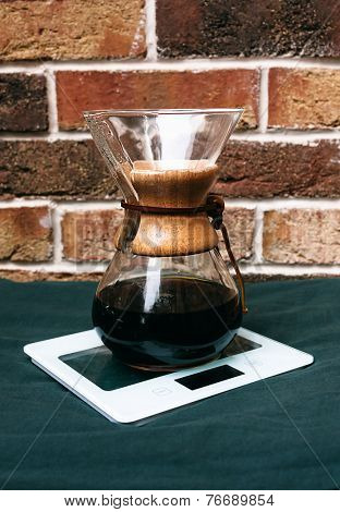 Old vintage wooden and glass coffee filter over a glass jug for brewing filter coffee manually standing on a counter in front of a rustic brick wall poster