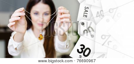 Woman keeping necklace with yellow sapphire at jeweler's shop, seasonal sale. Concept of wealth and luxurious life