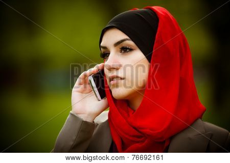 beautiful muslim woman wearing hijab outdoor and talking on the phone portrait