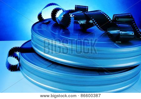 some film strips and metal movie film reel canisters on a table with a blue toning