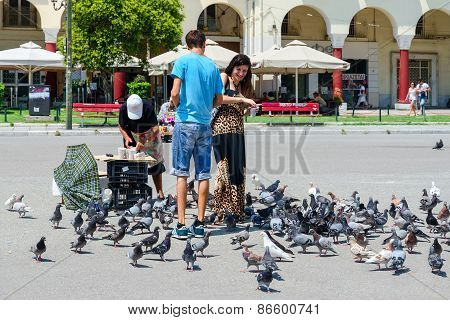 Young Man And Woman Are Feeding Pigeons In Square Of Aristotle In Thessaloniki