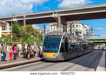 NICE, FRANCE - AUGUST 23, 2014: Modern tramway at tram stop. Nice tramway is single-line tramway opened on November 24, 2007 replacing old bus lines and providing a frequency of five minutes.