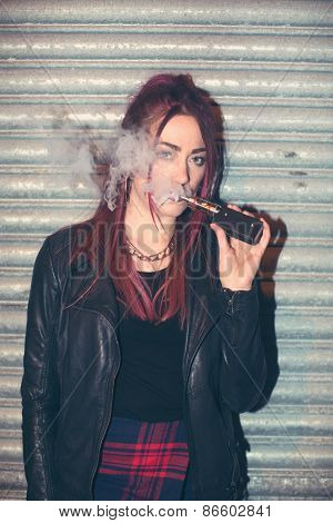 Trendy young woman puffing on an e-cigarette exhaling a cloud of smoke from the atomiser as she enjoys the pleasure of smoking nicotine in solution to simulate tobacco poster