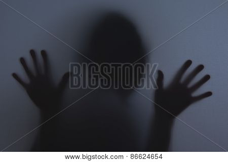 Shadowy figure behind glass / fear panic concept