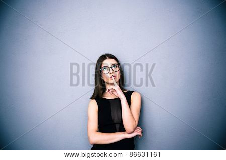 Young charming woman in glasses with finger over lips standing over gray background. Looking up at copyspace. Wearing in black fashion dress