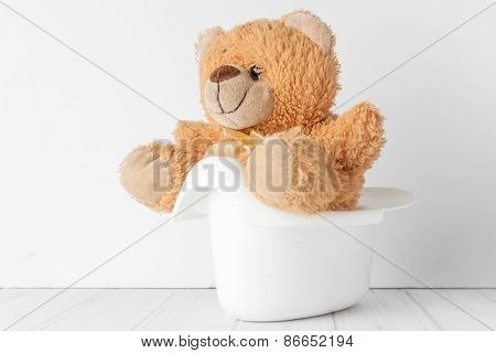 a teddy bear in a potty next to stack of diapers