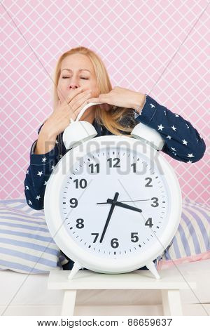 Blond woman of mature age with insomnia and big alarm clock