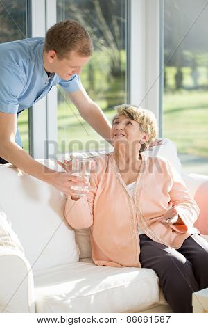 Male care assistant caring about elder woman poster
