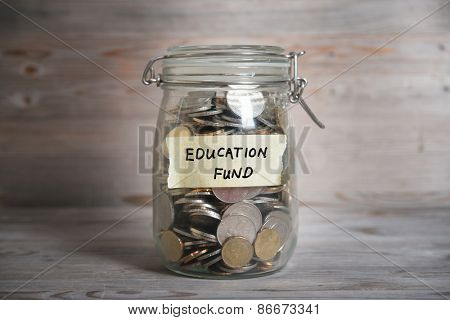 Coins in glass money jar with education fund label, financial concept. Vintage wooden background with dramatic light.