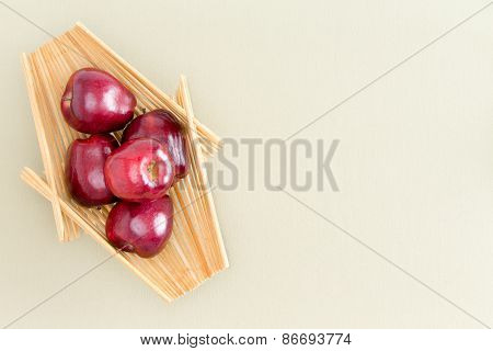 Healthy Fresh Red Apples on a Wooden Tray Placed on Top of a Light Green Table Emphasizing Copy Space. Captured in High Angle View. poster
