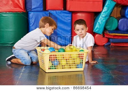 Childrean cleaning up balls in gym together in a preschool