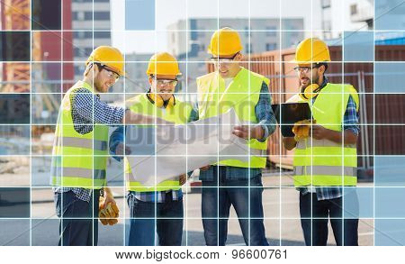 business, building, teamwork, technology and people concept - group of smiling builders in hardhats and highly visible vests looking at blueprint and clipboard outdoors over squared grid background
