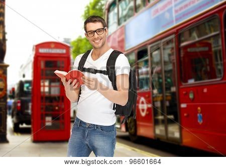 people, travel, tourism and education concept - happy young man with backpack and book over london city city bus on  street background