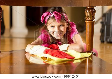 Portrait Of Smiling Girl Polishing Wooden Table With Cloth