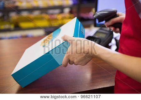 Female worker scanning cereal box at supermarket