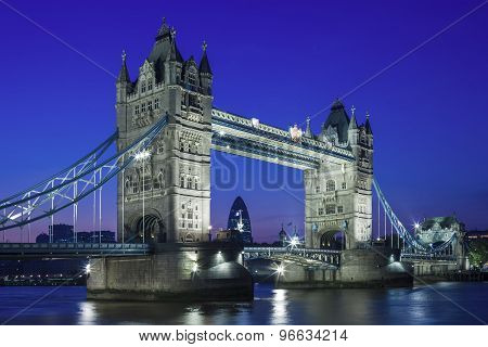 Illuminated Tower Bridge At Night And The City Of London, England