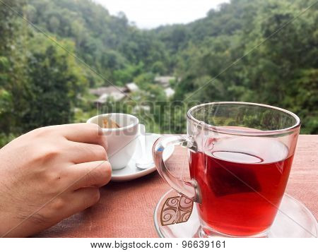 Hands Holding Coffee Cups And Resting On A Glass Of Tea On The Terrace With Mountain Views Behind.