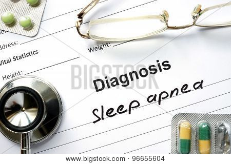 Diagnosis Sleep apnea and tablets on a wooden table.
