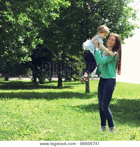 Life moment of happy family! Mother and son child playing having fun together outdoors at the weekend on the grass in sunny summer day poster