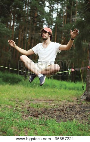 Sport leisure recreation and healthy lifestyle concept - man slacklining balancing on a rope slackline in forest poster
