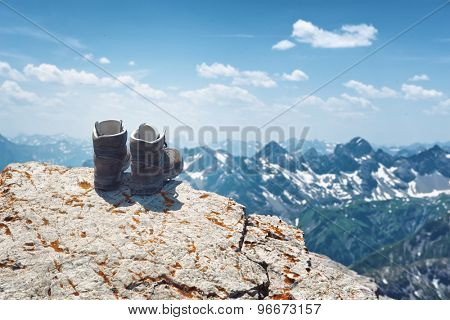 Pair of hiking boots on an alpine summit balanced on the edge of a rocky cliff overlooking distant alps with scattered snow on a sunny summer day, Hochvogel, Germany