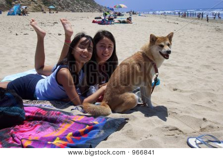 Girls With Their Dog At The Beach