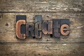 "word ""create"" written with vintage letterpress printing blocks on rustic wood background poster"