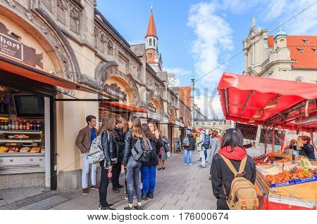 MUNICH BAVARIA GERMANY - APRIL 06 2016: Pedestrians browse shops and stalls beneath St. Peter's Church Peterskirche along Viktualienmarkt market street in Munich Bavaria Germany.