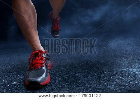 Asian man running on asphalt at night