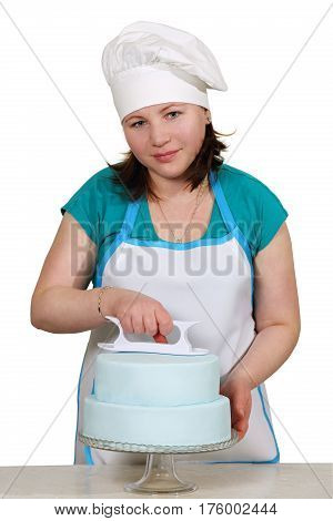 Chef smoothes mastic on the cake, isolated on a white background