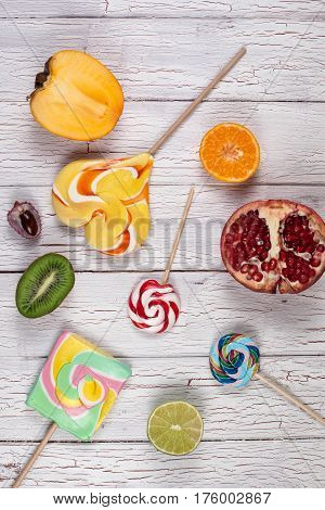 Composition of halved fruits and lollypops. White wooden board