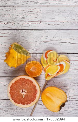 Fresh fruits cut into halves and colourful lollypop. Composition on a wooden board