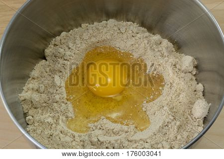 Gingerbread flour dry mix with egg in stainless steel mixing bowl