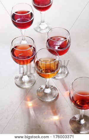 Glass of rose wine on white table