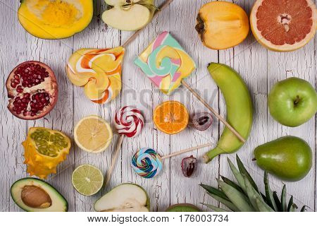 Composition of tropical fruits and sweet lollypops on a wooden board