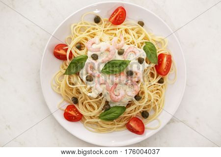spaghetti with white sauce and shrimps capers and tomato on a white plate
