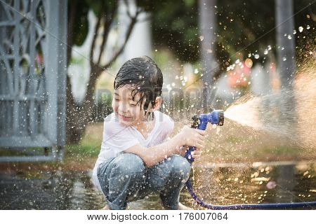 Cute asian boy has fun playing in water from a hose outdoors