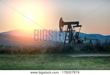 oil pump on orange sunset. Close up