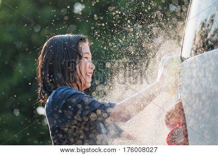 Asian girl washing car in the garden on summer day