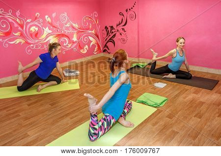 Trainer of fitness or yoga class sport women doing exercise in gym