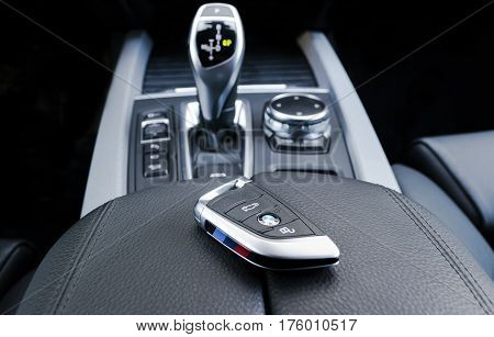 Sankt-Petersburg, Russia, March 05, 2017 - Close up of keys of BMW X5M 2017 in black leather car interior, gear stick background