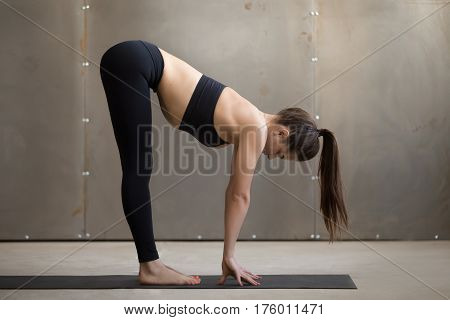 Young woman practicing yoga, doing Standing Half forward bend exercise, head to knees, Ardha uttanasana pose, working out, wearing black sportswear, cool urban style, full length, grey studio