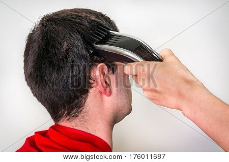 Hairdresser cutting black hair with electric hair clipper in barber shop
