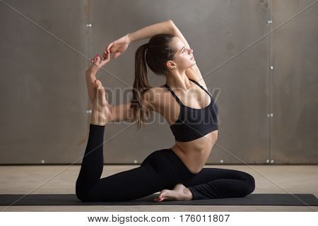 Young attractive woman practicing yoga, sitting in Mermaid exercise, Eka Pada Rajakapotasana pose, working out, wearing black sportswear, cool urban style, full length, grey studio background