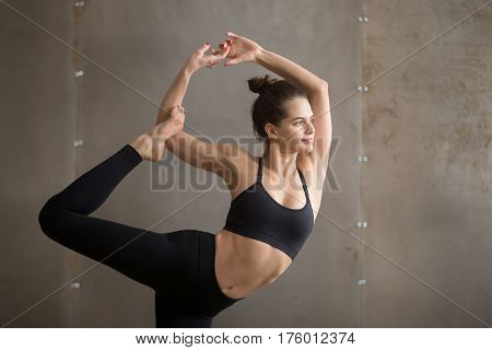 Portrait of young attractive smiling yogi woman practicing yoga, doing Natarajasana exercise, Lord of the Dance pose, working out wearing black sportswear, cool urban style grey studio background