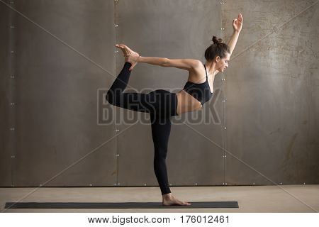Young attractive woman practicing yoga, standing in Natarajasana exercise, Lord of the Dance pose, working out, wearing black sportswear, cool urban style, full length, grey studio background